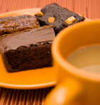 A Plate Of Chocolate Brownies And A Cup Of Coffee