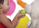 Kid Feeding Her Teddy An Apple