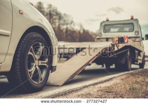 stock-photo-loading-broken-car-on-a-tow-truck-on-a-roadside-277327427