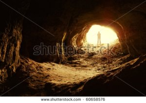 stock-photo-man-standing-in-front-of-a-cave-entrance-60658576