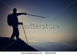 stock-photo-tourist-guide-show-the-right-way-with-pole-in-hand-hiker-with-sporty-backpack-stand-on-rocky-view-266942516