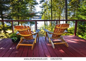 stock-photo-wooden-deck-at-forest-cottage-with-adirondack-chairs-116210701