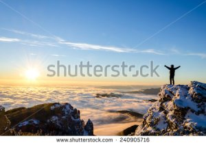 stock-photo-hiker-celebrating-success-on-top-of-a-mountain-in-a-majestic-sunrise-240905716