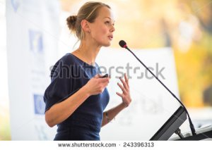 stock-photo-pretty-young-business-woman-giving-a-presentation-in-a-conference-meeting-setting-shallow-dof-243396313