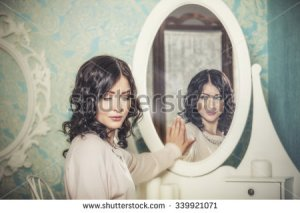stock-photo-beautiful-woman-in-the-mirror-reflected-the-smiles-magically-in-retro-interior-339921071