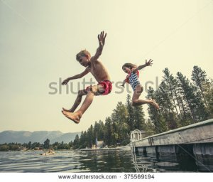 stock-photo-kids-jumping-off-the-dock-into-a-beautiful-mountain-lake-having-fun-on-a-summer-vacation-at-the-375569194