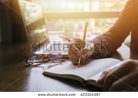 stock-photo-young-male-student-writes-information-from-portable-net-book-while-prepare-for-lectures-in-423324397