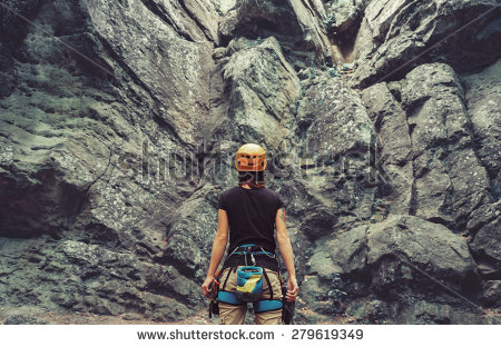 stock-photo-young-woman-wearing-in-climbing-equipment-standing-in-front-of-a-stone-rock-outdoor-and-preparing-279619349