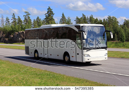 stock-photo-new-white-coach-bus-moves-along-freeway-through-beautiful-scenery-on-a-sunny-day-of-summer-547395385