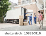 stock-photo-young-couple-watching-movers-move-boxes-from-the-moving-van-158330816