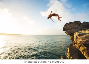 cliff-jumping-into-ocean-sunset-260nw-344995040